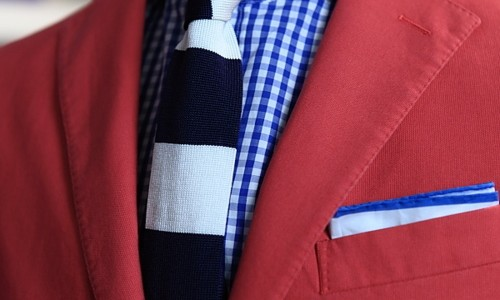 Colorful combo for men red blazer blue shirt and black and white tie.