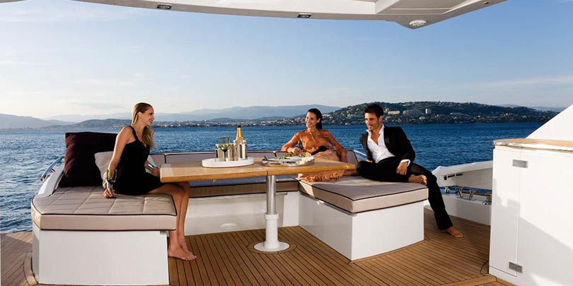 Guy with two models on a luxury yacht ealuxe