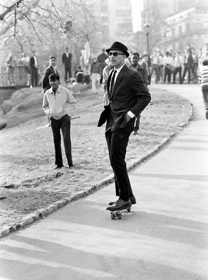 1965- Man In A Suit And Sunglasses Rides A Skateboard Down A Hill Path In Central Park, New York